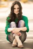 Chica joven que se sienta en una manera Imagen de archivo libre de regalías