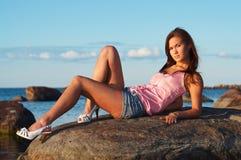Chica joven que se sienta en una piedra Foto de archivo