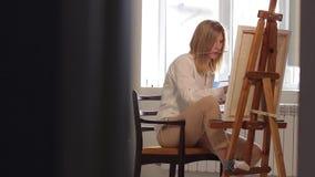 Chica joven que se sienta en una silla que dibuja una imagen metrajes