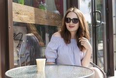 Chica joven que se sienta en una tabla en un café Fotografía de archivo