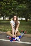Chica joven que se sienta a piernas cruzadas en el parque al lado del longboard y que mira la cámara Forma de vida al aire libre Imagen de archivo libre de regalías
