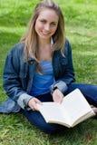 Chica joven que se sienta a piernas cruzadas mientras que sostiene un libro Foto de archivo