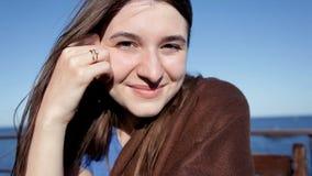 Chica joven que se sienta por el mar que sonríe y que presenta para la cámara almacen de video