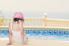 Chica joven que se sienta por la piscina Imagenes de archivo