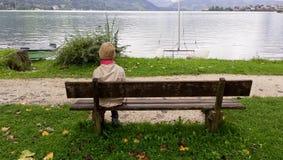 Chica joven que se sienta solamente en un banco Imagen de archivo libre de regalías