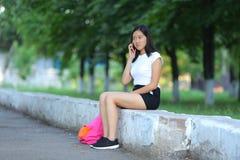 Chica joven que se sienta y que habla en el teléfono en el parque Fotos de archivo libres de regalías