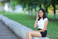 Chica joven que se sienta y que habla en el teléfono en el parque Imagenes de archivo