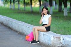 Chica joven que se sienta y que habla en el teléfono en el parque Fotos de archivo