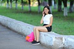 Chica joven que se sienta y que habla en el teléfono en el parque Imagen de archivo