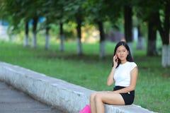 Chica joven que se sienta y que habla en el teléfono en el parque Imagen de archivo libre de regalías