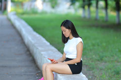Chica joven que se sienta y que habla en el teléfono en el parque Foto de archivo