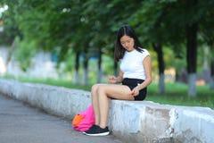 Chica joven que se sienta y que habla en el teléfono en el parque Imágenes de archivo libres de regalías