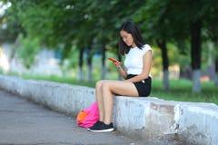 Chica joven que se sienta y que habla en el teléfono en el parque Fotografía de archivo libre de regalías