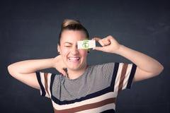 Chica joven que se sostiene de papel con la muestra de dólar verde Imagen de archivo libre de regalías