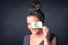 Chica joven que se sostiene de papel con la muestra de dólar verde Fotografía de archivo