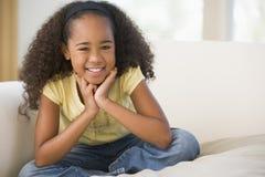 Chica joven que sienta Legged cruzado en un sofá en el país Imagen de archivo