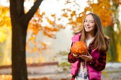 Chica joven que sonríe alegre con una calabaza en sus manos Imagenes de archivo