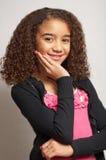 Chica joven que sonríe con la mano en la barbilla Fotos de archivo