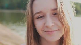 Chica joven que sonríe con sonrisa perfecta y los dientes blancos en un parque y que mira la cámara almacen de metraje de vídeo