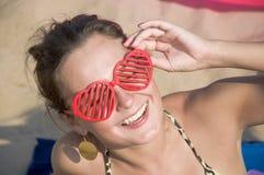 Chica joven que sonríe en gafas de sol rojas Imagen de archivo