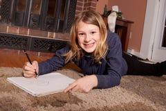 Chica joven que sonríe y que dibuja Imagen de archivo libre de regalías