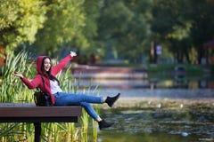 Chica joven que sonríe y que habla en el teléfono celular al aire libre Fotos de archivo libres de regalías