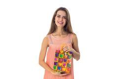 Chica joven que sonríe y que lleva a cabo un paquete Imagen de archivo libre de regalías
