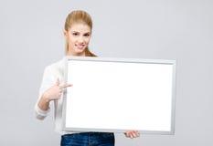 Chica joven que sonríe y que señala a un tablero en blanco blanco. Fotos de archivo