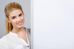 Chica joven que sonríe y que se coloca cerca de un tablero en blanco blanco. Fotos de archivo libres de regalías