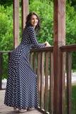 Chica joven que sonríe y que se coloca cerca de la verja de madera en la naturaleza Fotos de archivo libres de regalías