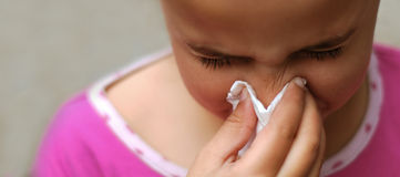 Chica joven que sopla su nariz Imagenes de archivo