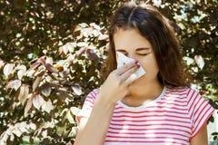 Chica joven que sopla su nariz Chica joven con alergia en parque del otoño Imagen de archivo
