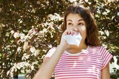 Chica joven que sopla su nariz Chica joven con alergia en parque del otoño Foto de archivo libre de regalías