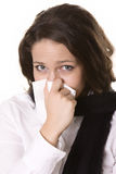 Chica joven que sopla su nariz en el tejido Fotos de archivo