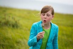 Chica joven que sopla un diente de león Foto de archivo