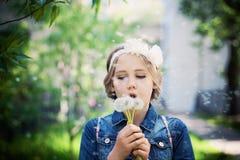 Chica joven que sopla un diente de león al aire libre Imagen de archivo