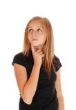 Chica joven que sostiene el finger en la barbilla Imagen de archivo
