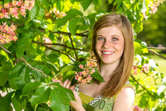 Chica joven que sostiene el flor en parque soleado Imagen de archivo libre de regalías