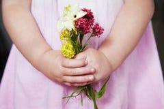 Chica joven que sostiene el manojo de flores salvajes Fotos de archivo