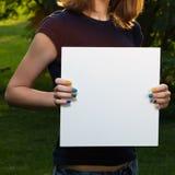 Chica joven que sostiene el papel en blanco blanco Imágenes de archivo libres de regalías