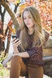 Chica joven que sostiene el teléfono móvil disponible y que mira la pantalla Fotos de archivo libres de regalías