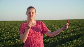 Chica joven que sostiene la fresa disponible en el fondo de la plantación de la fresa almacen de metraje de vídeo