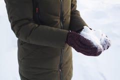 Chica joven que sostiene la nieve en sus manos en manoplas, invierno, diversión, alegría, deportes, reconstrucción, niños imagen de archivo libre de regalías