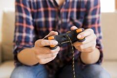 Chica joven que sostiene la palanca de mando mientras que juega a los videojuegos Fotografía de archivo libre de regalías
