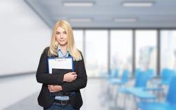 Chica joven que sostiene los cuadernos en una sala de conferencias Foto de archivo libre de regalías