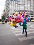 Chica joven que sostiene los globos para la venta Foto de archivo libre de regalías