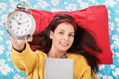 Chica joven que sostiene su libro y despertador preferidos Imagen de archivo