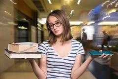 Chica joven que sostiene un libro en una mano y una tableta-PC en el más allá del horizonte Fotografía de archivo