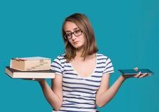 Chica joven que sostiene un libro en una mano y una tableta-PC en el ot Fotos de archivo