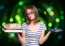 Chica joven que sostiene un libro en una mano y una tableta-PC en el ot Foto de archivo libre de regalías